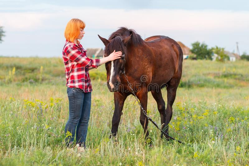 Red-haired girl in a red plaid shirt stroking a brown horse royalty free stock photos