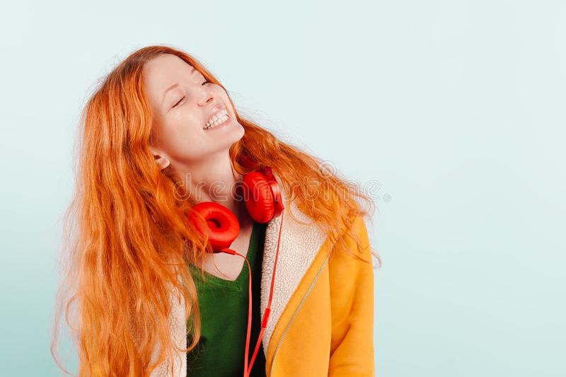 Red-haired girl in red headphones and yellow jacket laughs. Positive, happiness, joy and pleasure stock images