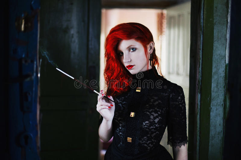 Red-haired girl with red lips in a dark room, a woman holds the mouthpiece with a cigarette in his hand stock images