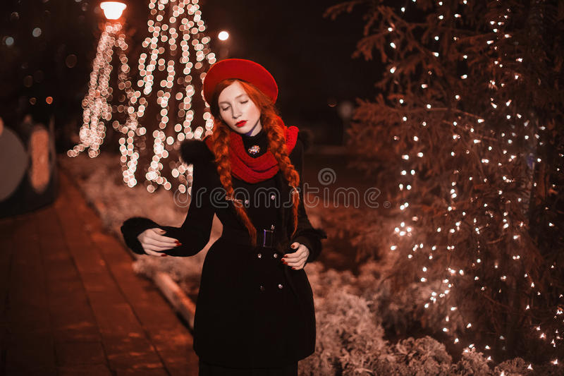 Red-haired girl with red lips in red beret and scarf standing against the background of the Christmas tree royalty free stock photography