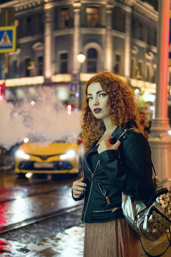 Red-haired girl smokes an electronic cigarette. Young red-haired girl smokes an electronic cigarette. She is walking in street of night city. Nicotine cigarette stock photos