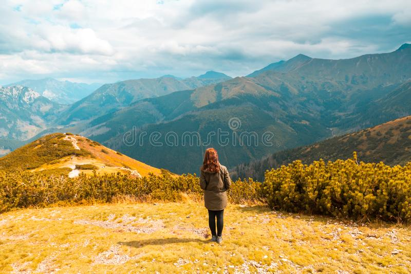 A red-haired girl stands against the background of a stunning autumn mountain landscape.  royalty free stock photo