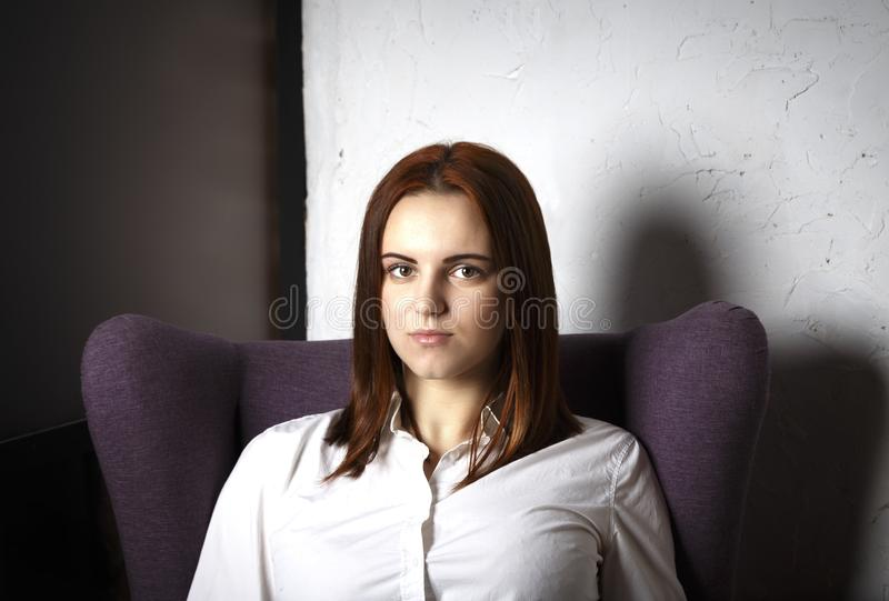 Red-haired girl student portrait in chair, loft interior, mysterious calm face stock photos