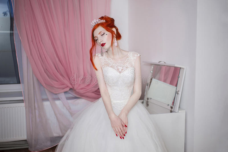 Red-haired girl in a wedding dress, bright unusual appearance, red nails, a girl with pale skin. Beautiful wedding dress, a heart on her cheek, bright make-up stock photo