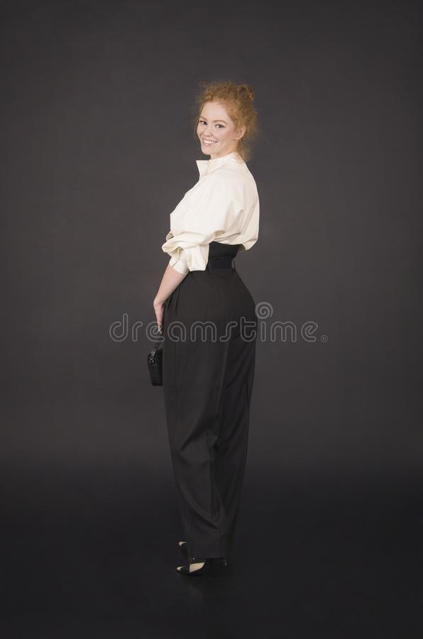 Red-haired girl in a white blouse and dark trousers. Studio shooting on a dark background stock photo