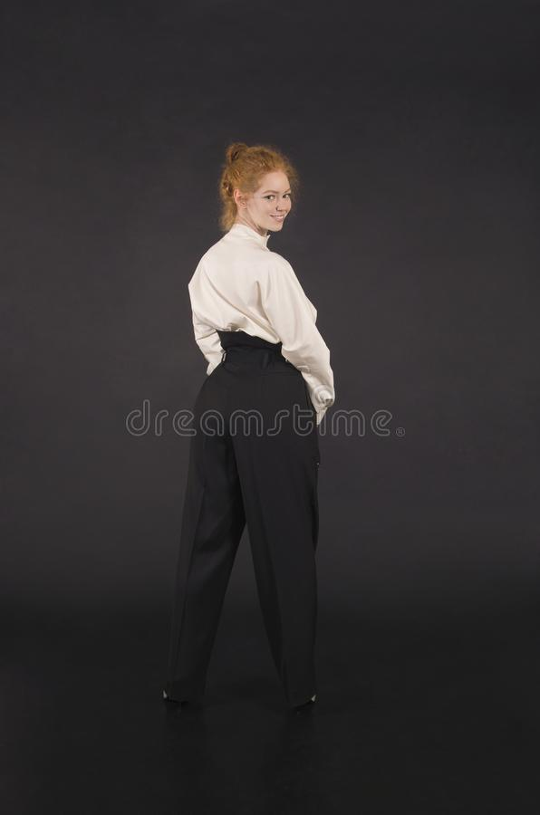 Red-haired girl in a white blouse and dark trousers. Studio shooting on a dark background royalty free stock photos