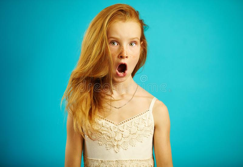 Red haired girl in white dress with surprised expression opens her mouth and eyes wide, shows a strong emotion of fear royalty free stock image