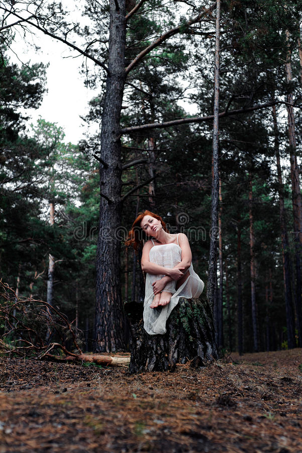Red-haired girl in the woods royalty free stock photography