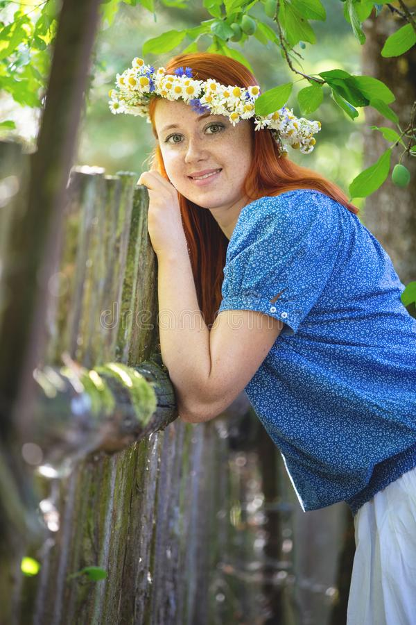 Red-haired girl with a wreath on his head stock photography