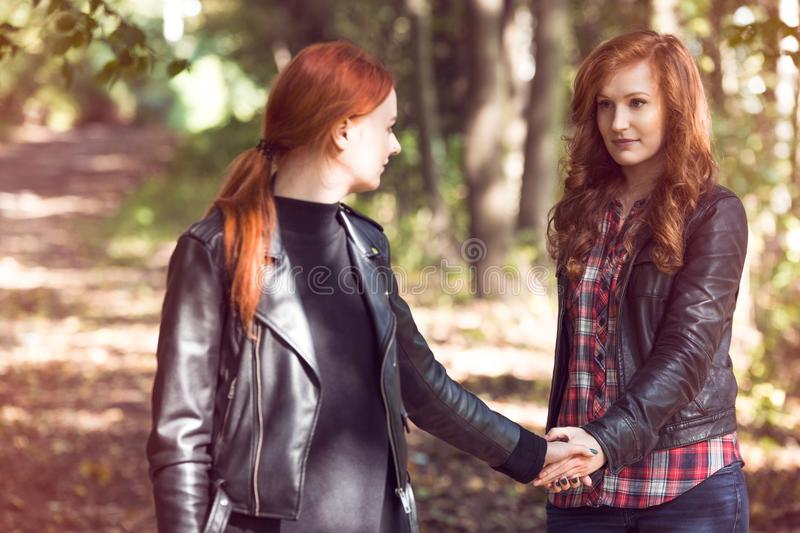 Red-haired girlfriends in the forest stock photography