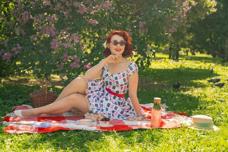 Red-haired happy pin up girl in vintage summer dress and classic stockings with a seam in the back sits on a blanket  on the green stock photos