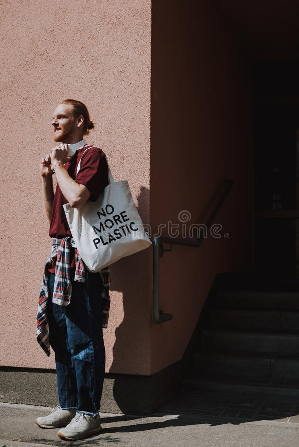 Red haired hipster man going to walk. Urban lifestyle and safe environment. Full length side on portrait of young happy red haired hipster guy with headphones royalty free stock image