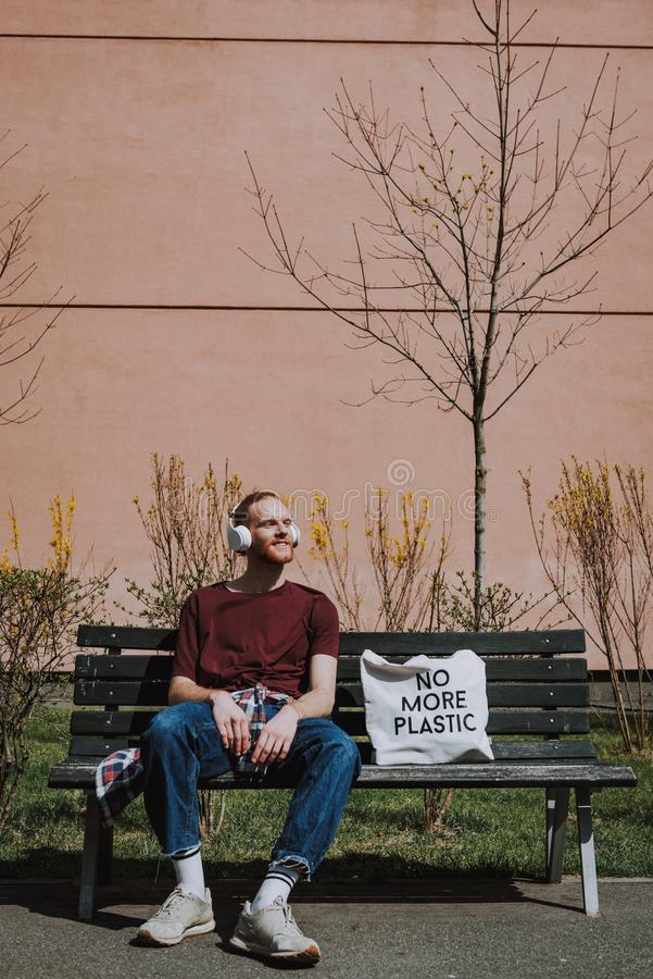 Red haired hipster man sitting on bench. Urban lifestyle and safe environment. Full length portrait of young happy hipster guy with headphones on head and eco royalty free stock images