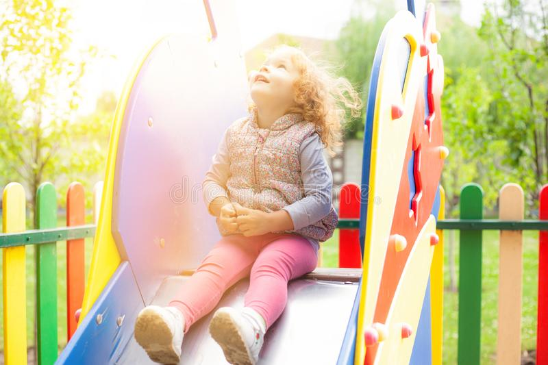 Red-haired little girl sits on a childrens slide in the park and looks into the bright sky stock photography