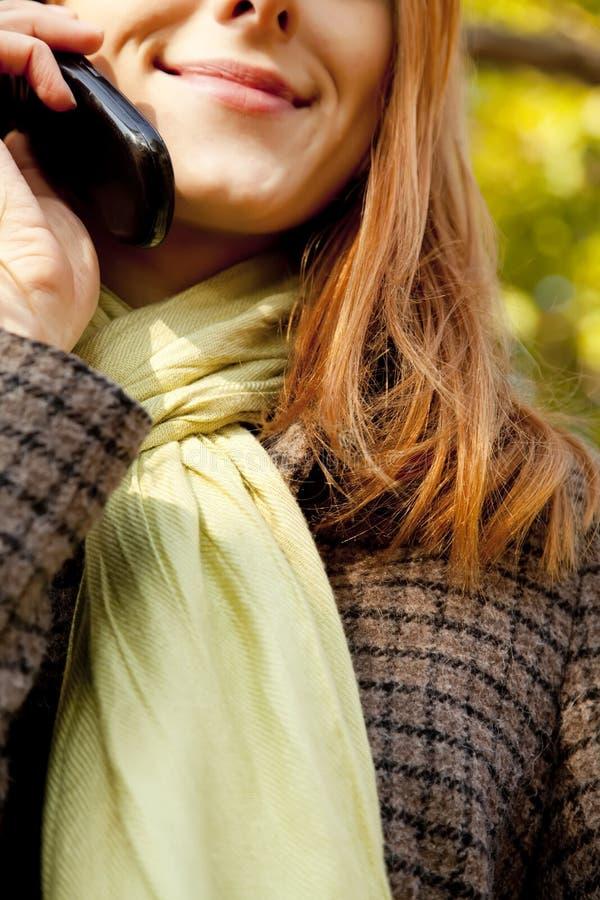 Red-haired Mädchen, das durch das Telefon benennt stockfoto