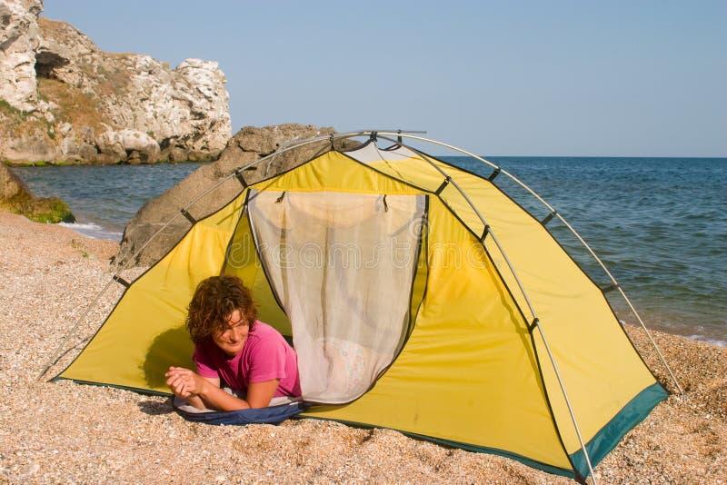 Red-haired Mädchen im Schlafenbeutel nahe des Zeltes stockfotos