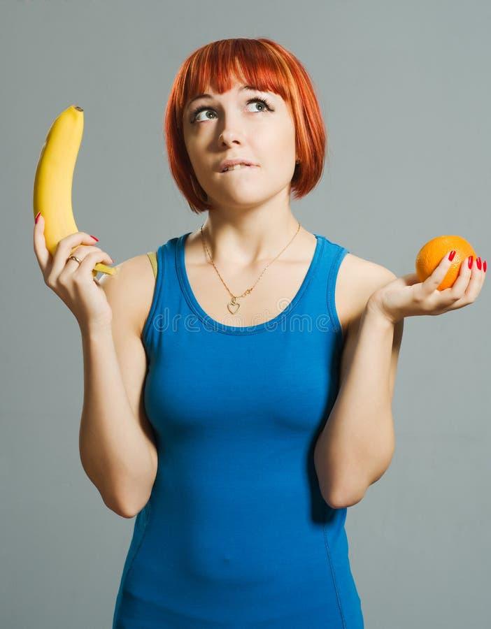 Red-haired Mädchen mit Banane stockfotos