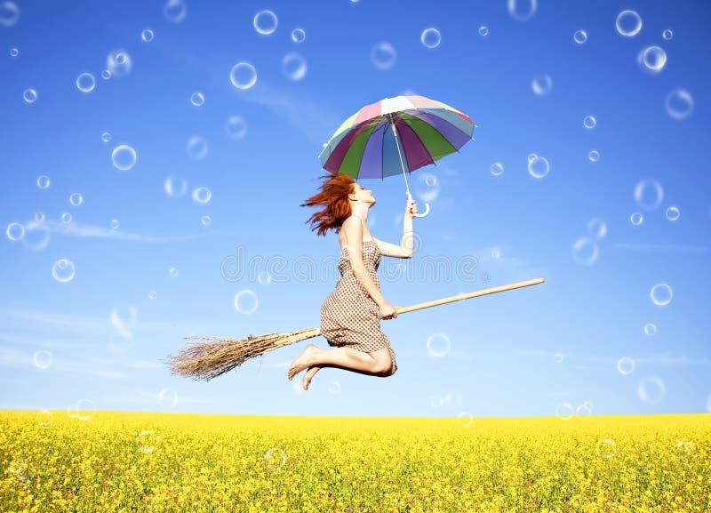 Red-haired Mädchenfliege mit Regenschirm lizenzfreie stockbilder