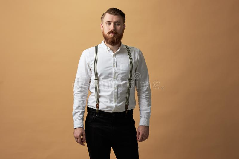 Red-haired man with beard dressed in a white shirt and black trousers with suspender stands on a beige background in the royalty free stock image