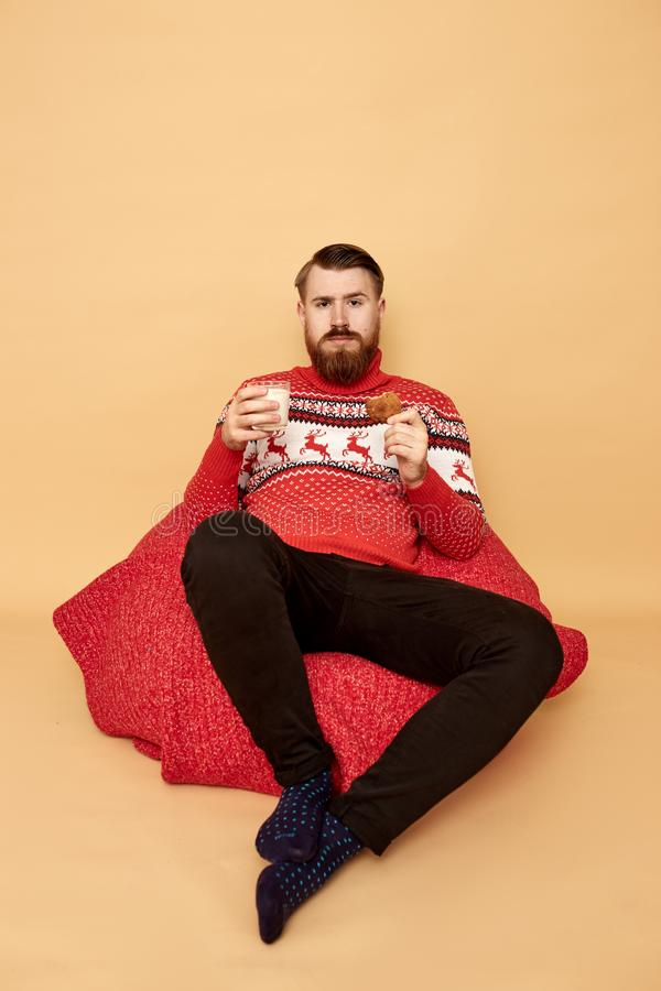 Red-haired man with beard dressed in a red and white sweater with deer and red cape sits on the floor and holds a glass royalty free stock image