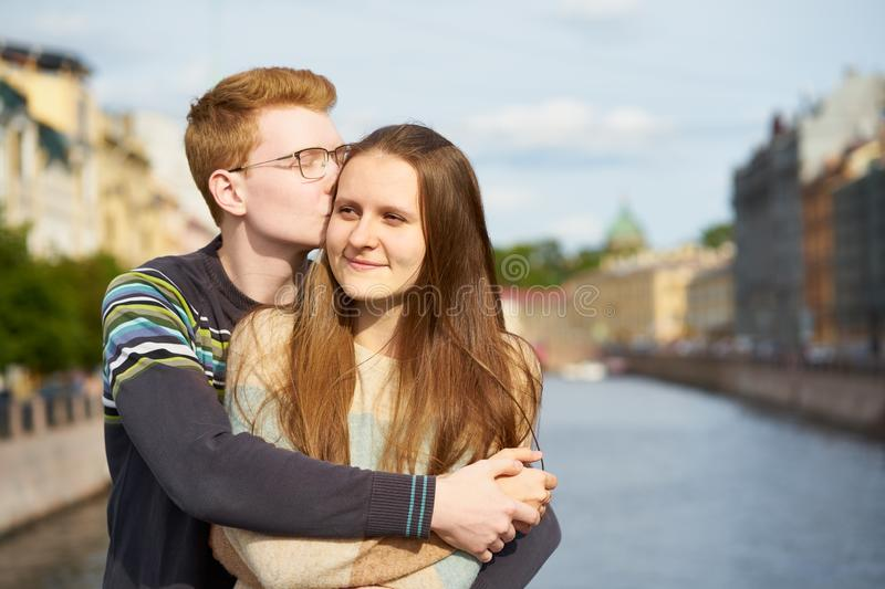 Red-haired man kisses a woman on her hear, a boy in a sweater comforts a girl with long dark thick hair stock images