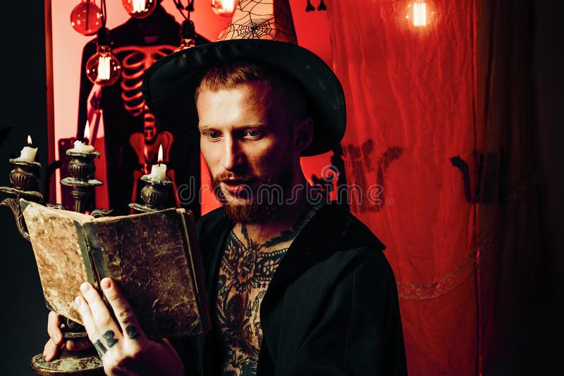 Red-haired man reading a magic book with spells. Happy father on halloween background with magik book. Magic hat. Holiday halloween with funny carnival royalty free stock photo