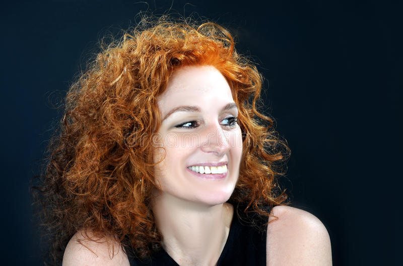 Red haired mid aged woman. Portrait of an mid aged attractive woman with red curled hair stock image