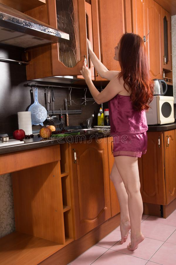 Red-haired middle-aged woman in the kitchen opens the cabinet door.  royalty free stock photo