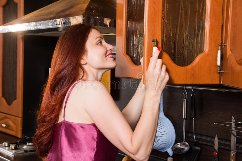 Red-haired middle-aged woman in the kitchen opens the cabinet door.  stock image