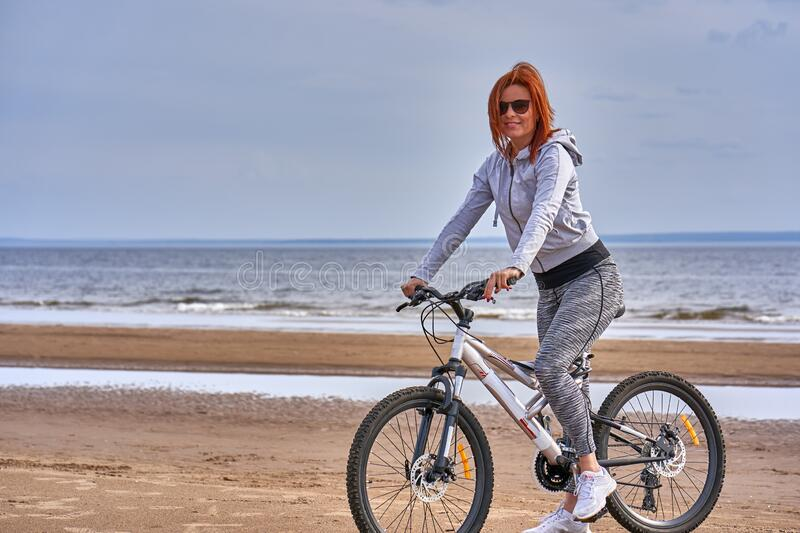 Red-haired middle-aged woman in sportswear on a bike walk on the sandy shore of a large river. stock image