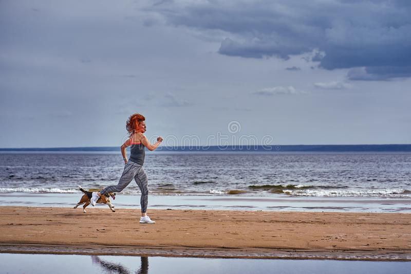 A red-haired middle-aged woman in sportswear runs along the sandy shore of a large river with her puppy. On a cloudy summer morning. Healthy lifestyle stock photo