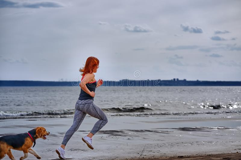 A red-haired middle-aged woman in sportswear runs along the sandy shore of a large river with her puppy. On a cloudy summer morning. Healthy lifestyle royalty free stock photo