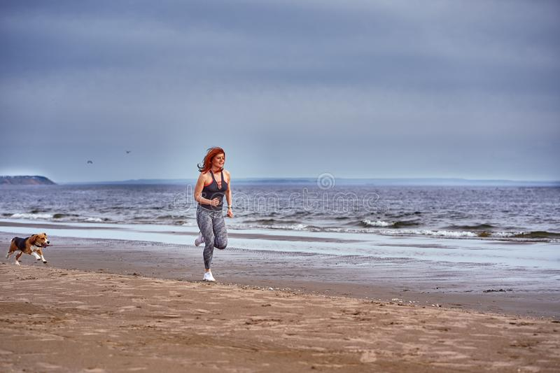 A red-haired middle-aged woman in sportswear runs along the sandy shore of a large river with her puppy. On a cloudy summer morning. Healthy lifestyle royalty free stock images