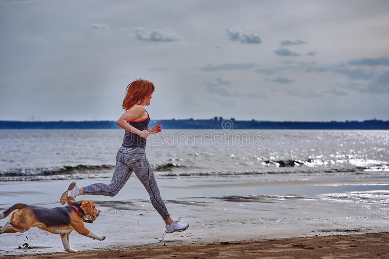 A red-haired middle-aged woman in sportswear runs along the sandy shore of a large river with her puppy. On a cloudy summer morning. Healthy lifestyle stock photos