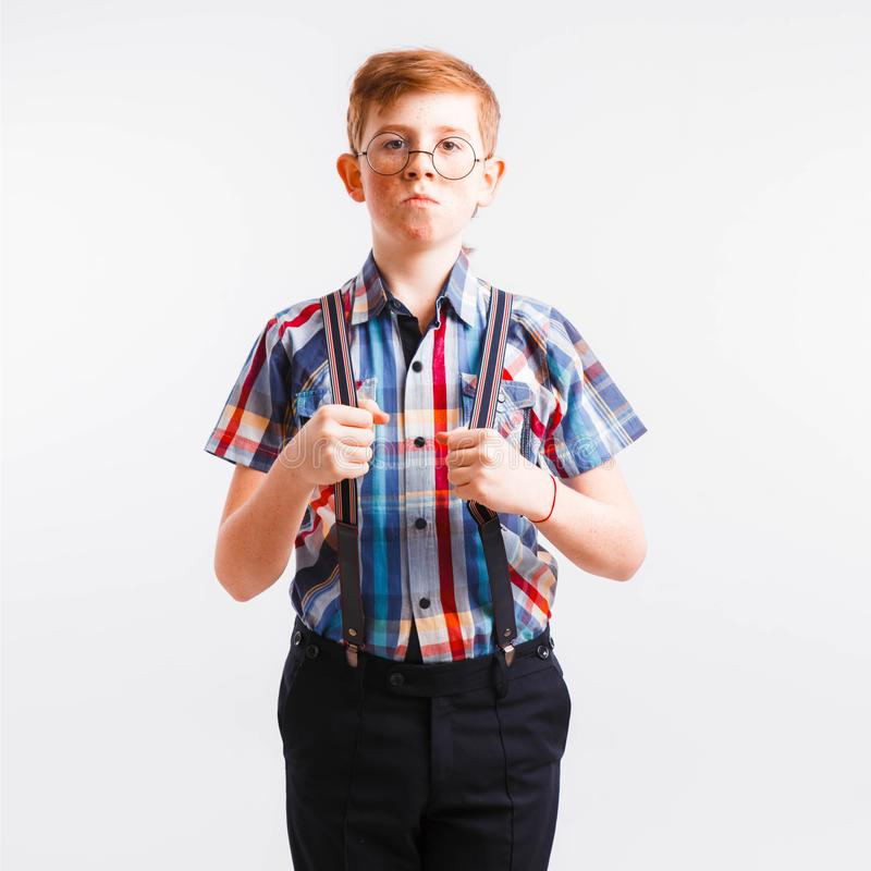 Red-haired nerd with braces and glasses on a white background. Space for text stock images