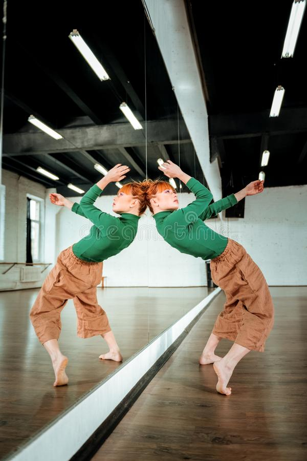 Red-haired professional dance teacher working out dancing movements. Contemporary dance. Red-haired professional dance teacher wearing a green turtleneck working stock image