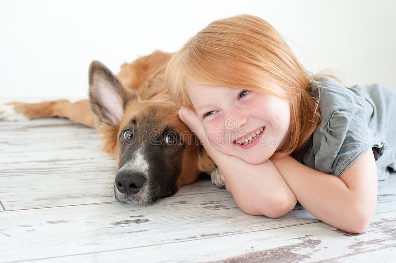 Red-haired puppy and red-haired girl. Lie on the floor stock images