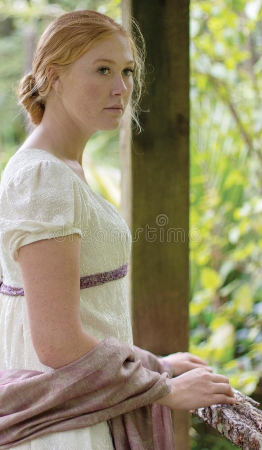 Regency woman in cream dress walks alone in a summer garden stock images