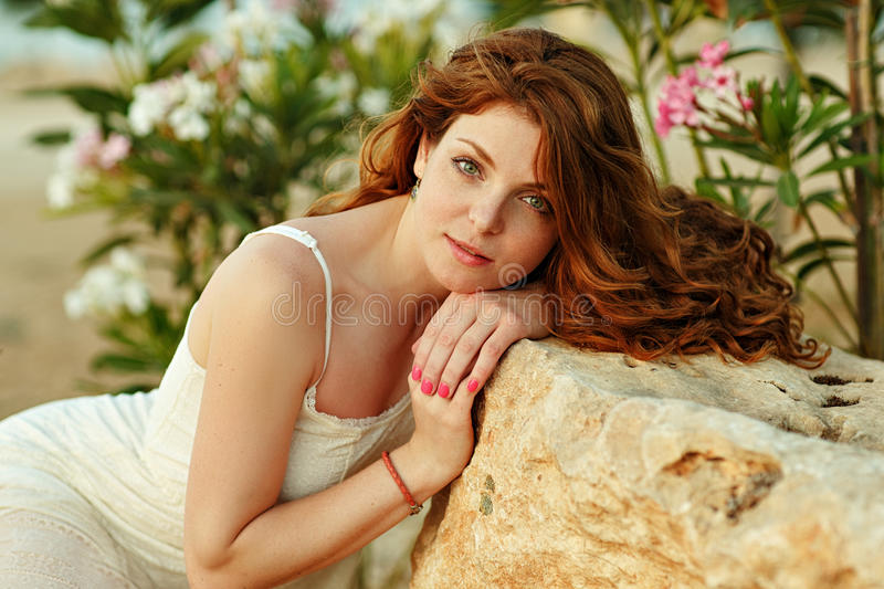 The red-haired sensual girl with freckles on a background of yellow rocks at sunset in summer royalty free stock images