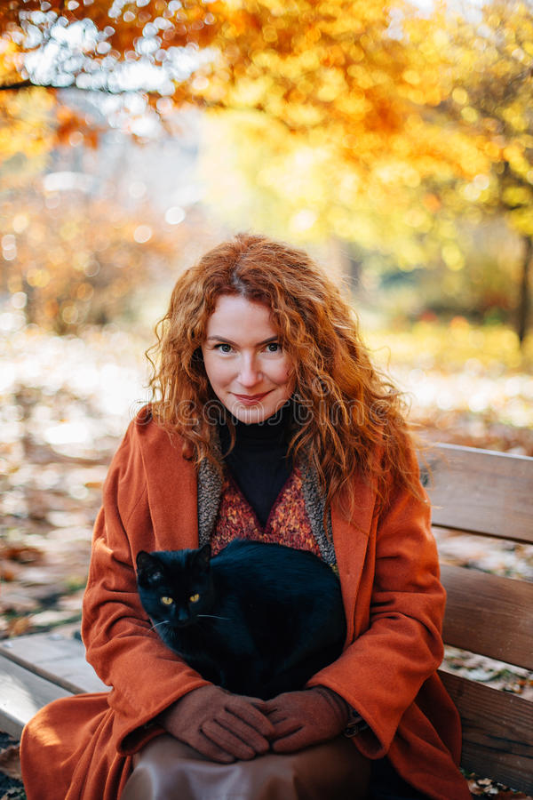 Red-haired smiling beautiful woman with black cat royalty free stock photography