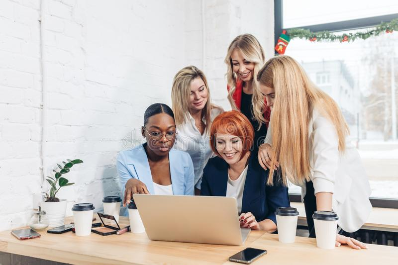 Red-haired teacher explaining new material on economics to female students. royalty free stock photos
