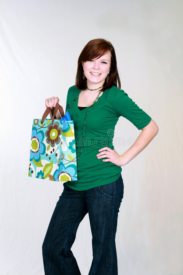 Red haired teen girl with shopping bag royalty free stock photography