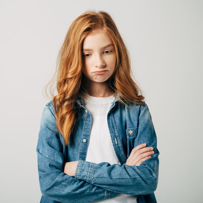 The red-haired teen girl is very offended by her parents. The blue-eyed cutie is upset. She is angry and look at the royalty free stock photos