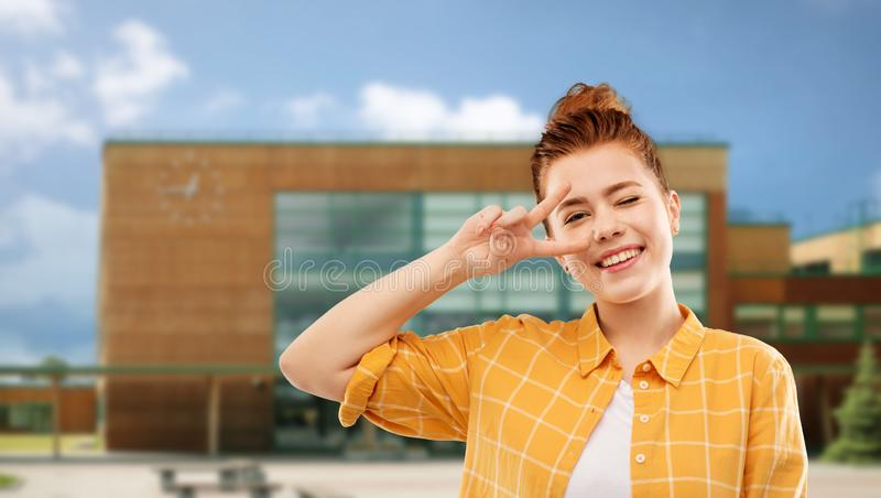 Red haired teenage girl showing peace over school royalty free stock photo