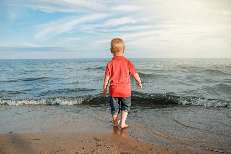 Toddler child kid in red t-shirt and jeans standing near water on lake sea ocean beach at evening sunset looking far away. stock photos