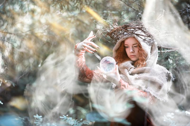 Red-haired witch in a dense forest. With a crystal ball and herbsr stock image