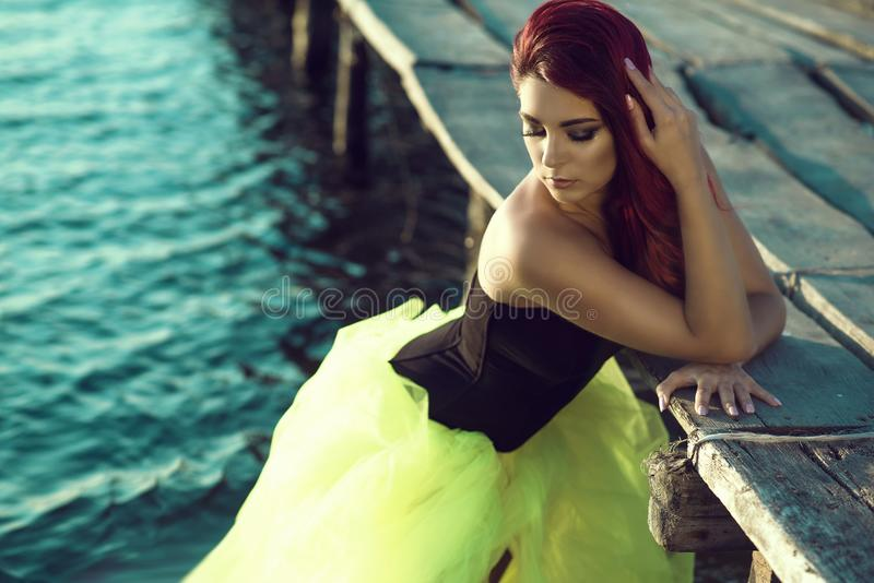 Red haired woman in black corset and long tail green veiling skirt standing in the sea water leaning on the pier. Mermaid concept royalty free stock photos