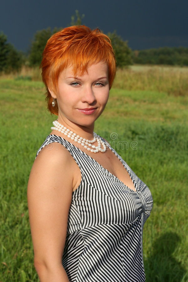 Red-haired woman in dress royalty free stock photos