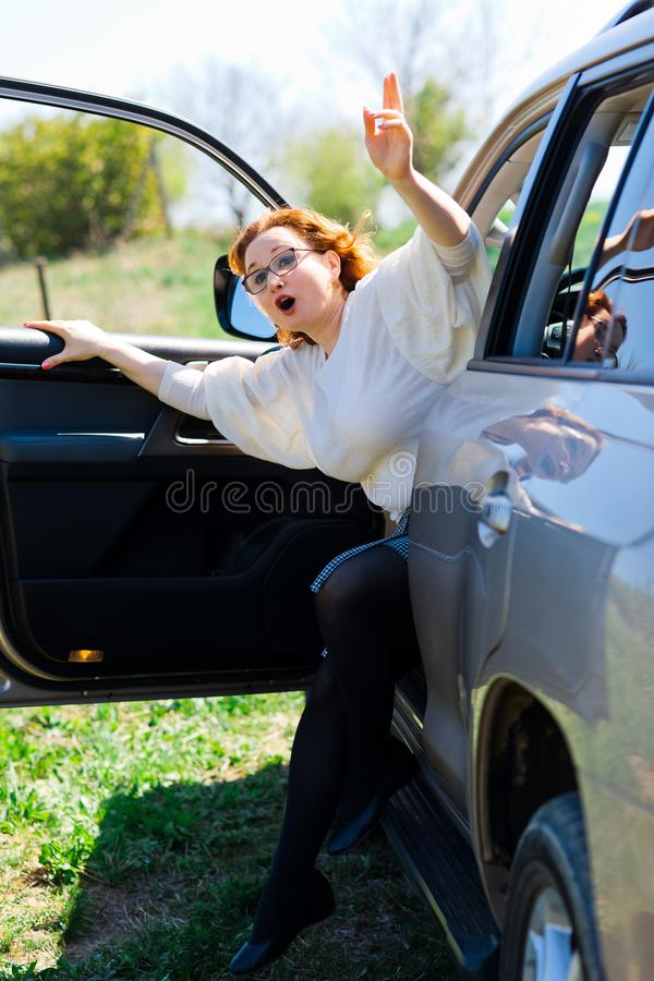 A red haired woman getting our of a car to call help stock image