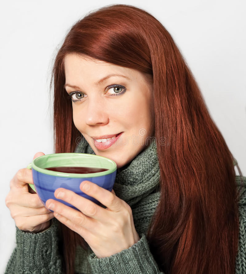 Red-haired woman holding cup royalty free stock photos